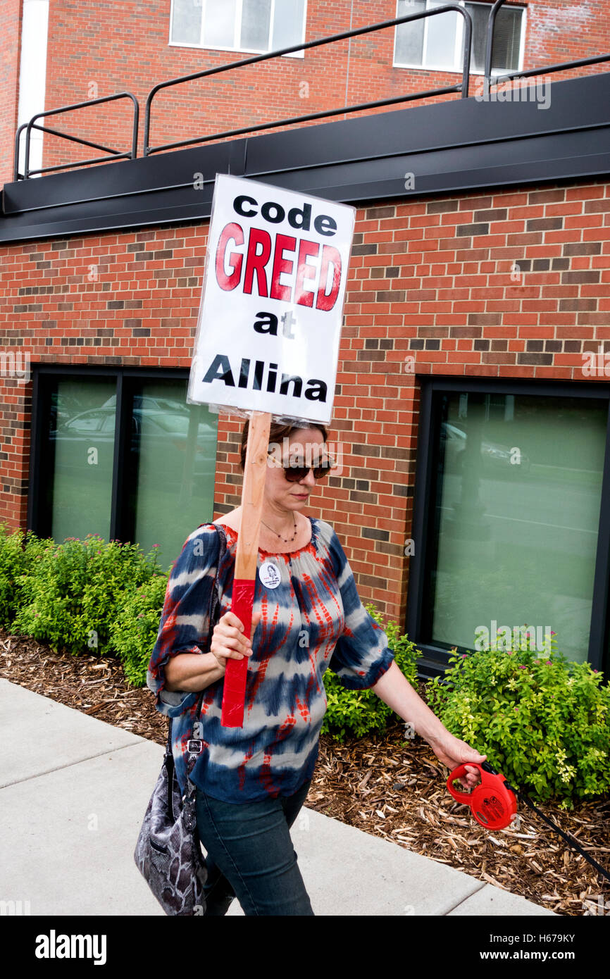 Striking nurse carrying a 'Code Greed' sign protesting new health benefits package and security. Minneapolis - Stock Image