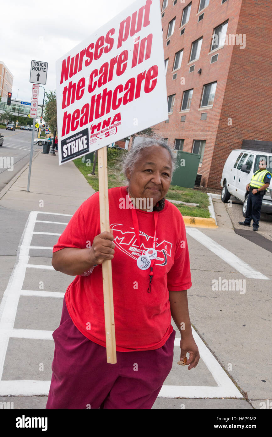 Mature ethnic woman nurse carrying placard protesting new health benefits package at Allina Health Minneapolis Minnesota - Stock Image