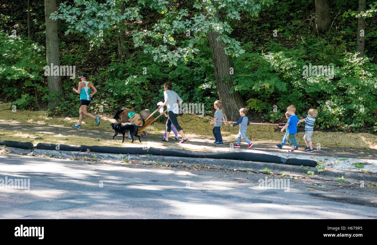 Daycare children hanging on to a rope on their way to a picnic at Lake Harriet. Minneapolis Minnesota MN USA Stock Photo