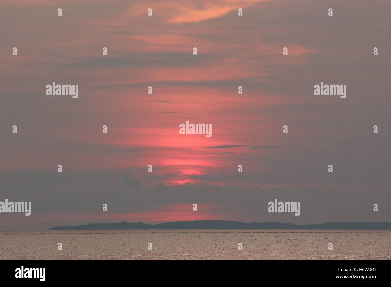 Sunset behind the sky over Mabini Beach - Stock Image