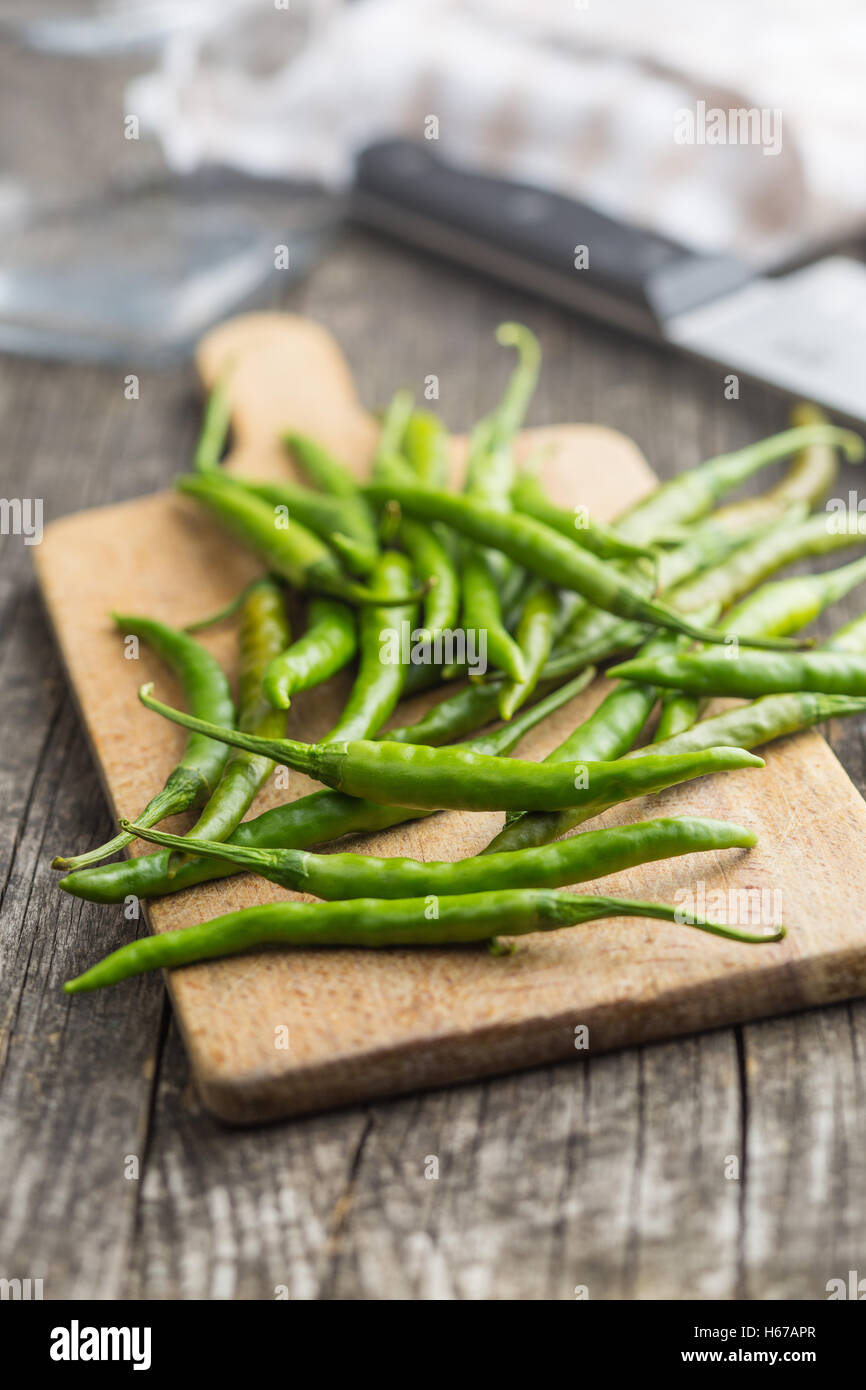 Green chili peppers on cutting board. - Stock Image