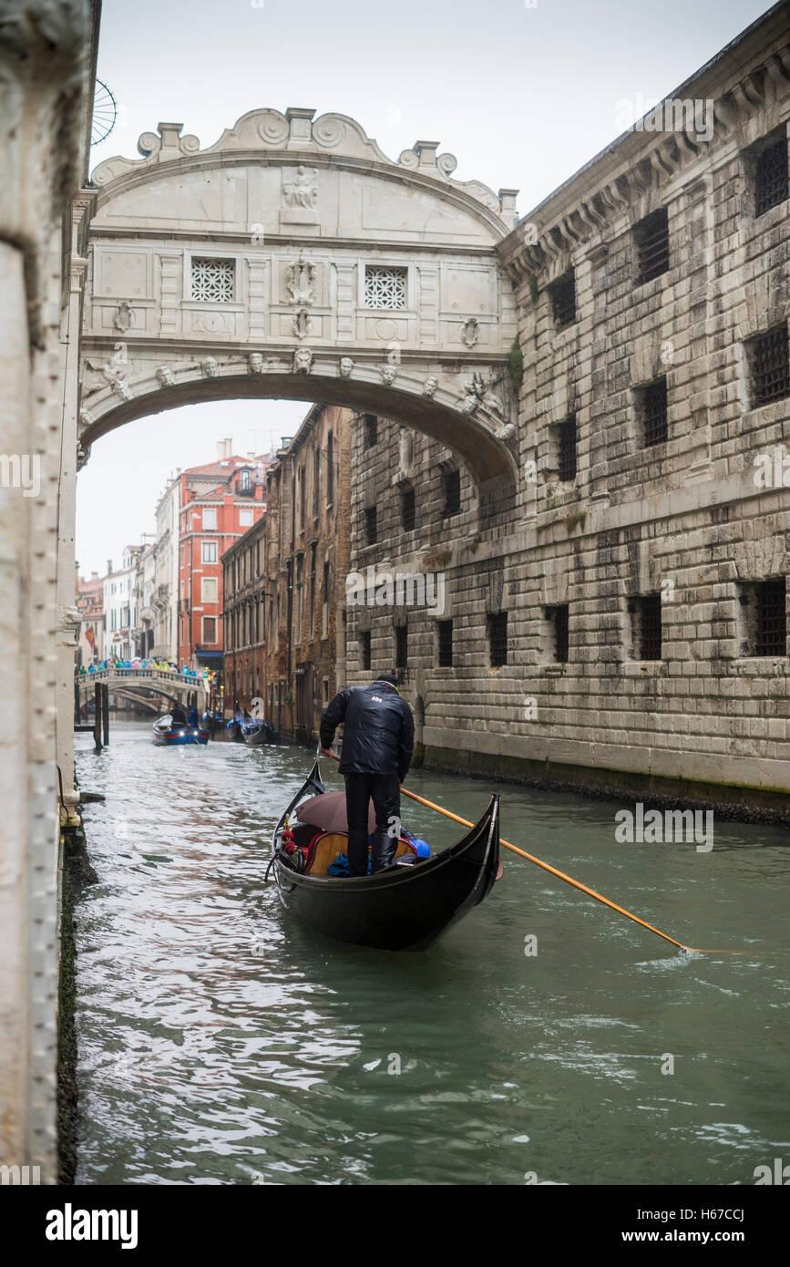 Gondolas travel next to Doge's Palace under the Bridge of Sighs (Ponte dei Sospiri), Venice, Italy, EU, Europe - Stock Image