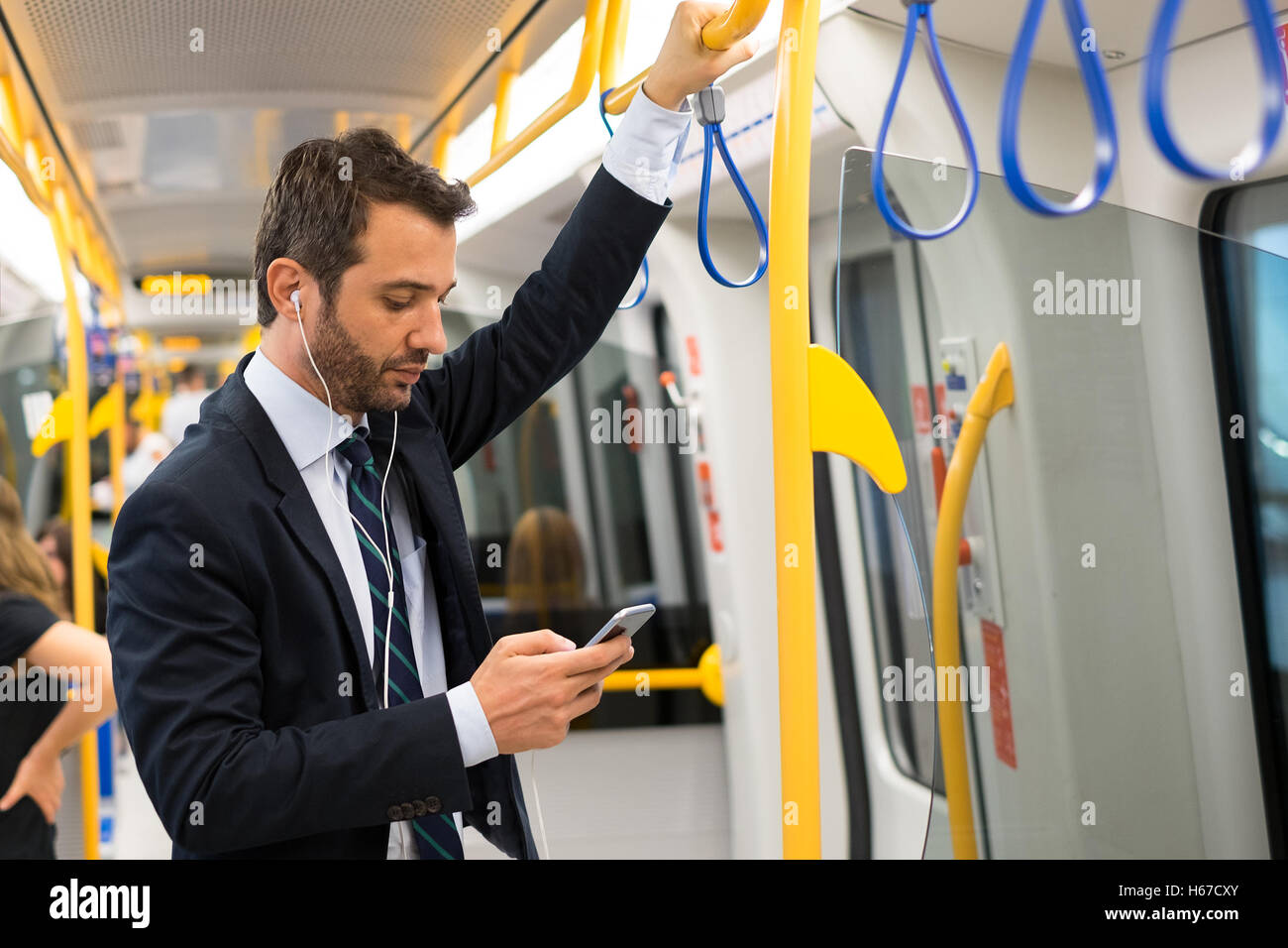 Businessman commuter traveling on the metro underground - Stock Image