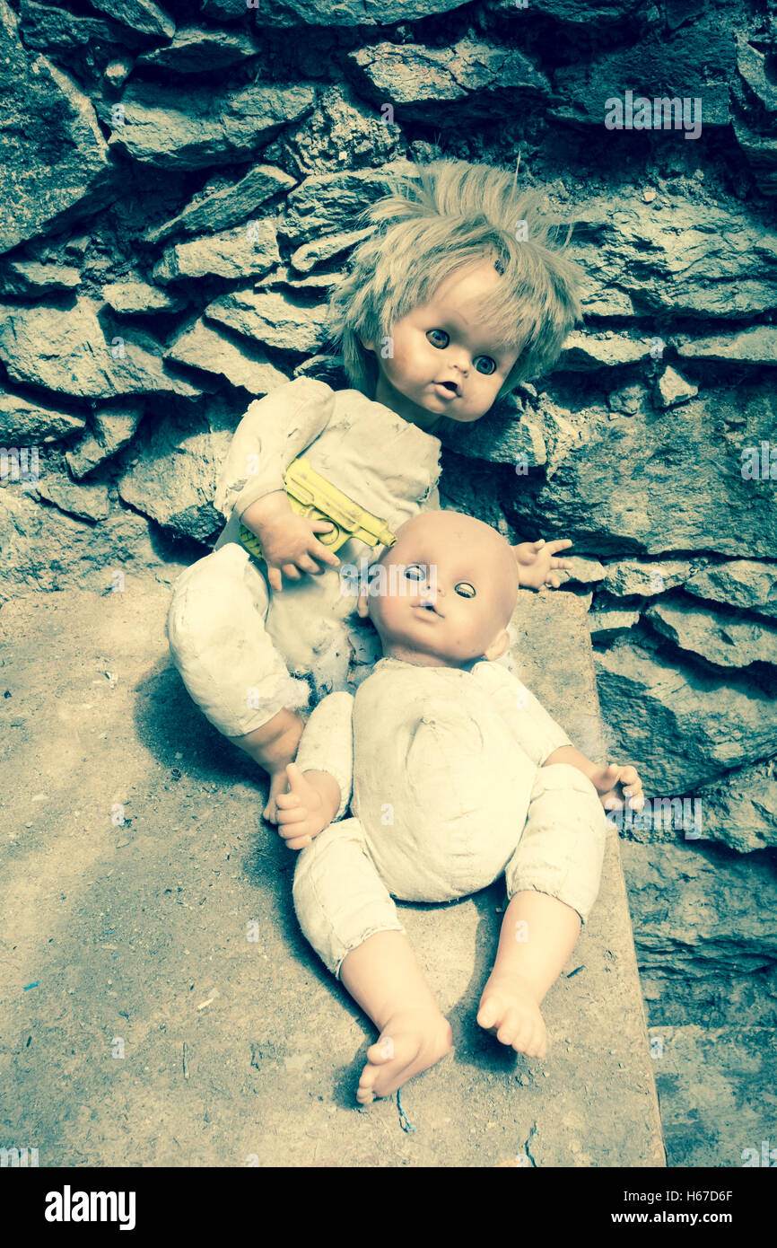 Two dolls, one holding plastic gun to head of other doll, in derelict mountain house - Stock Image