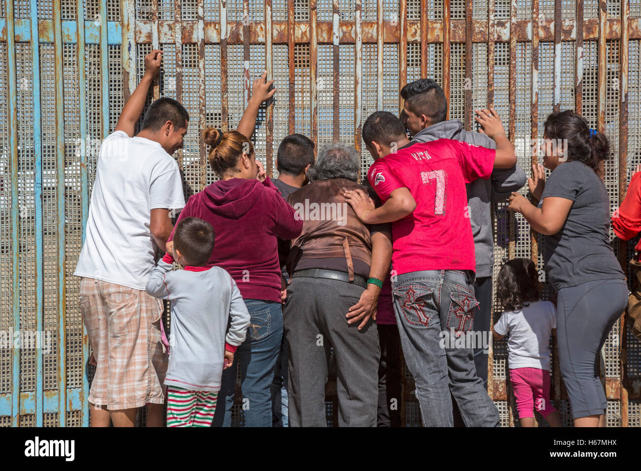 Tijuana, Mexico - Family members separated by deportation visit through the U.S.-Mexico border fence. - Stock Image