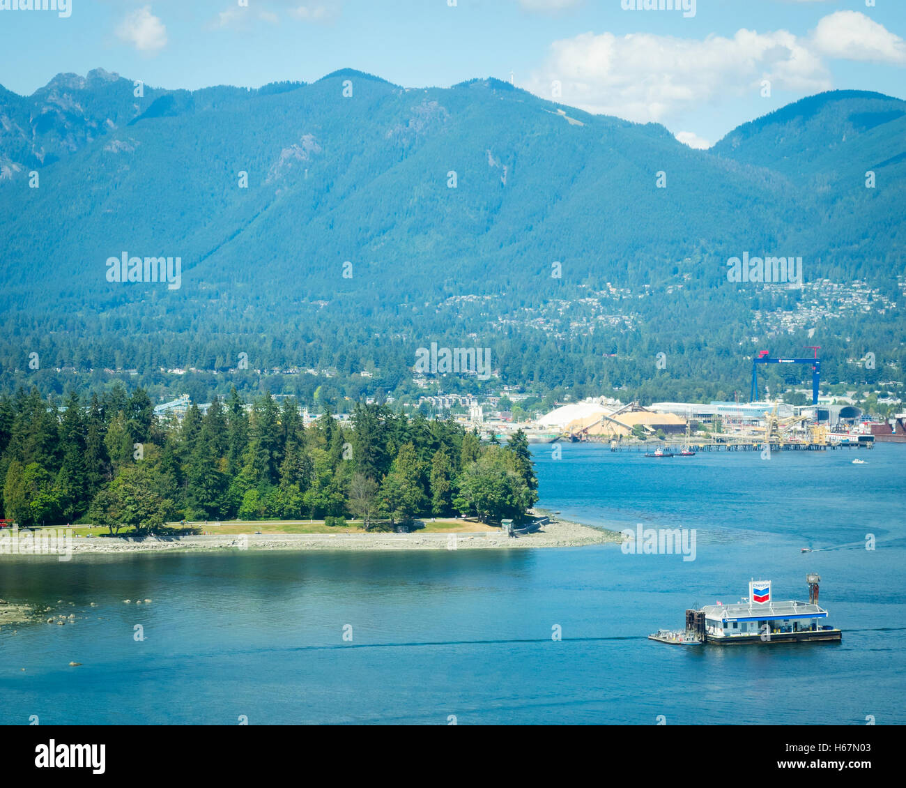 Elevated view: Coal Harbour, the floating Chevron fuel station, Stanley Park, Vancouver Harbour, and Grouse Mountain. - Stock Image