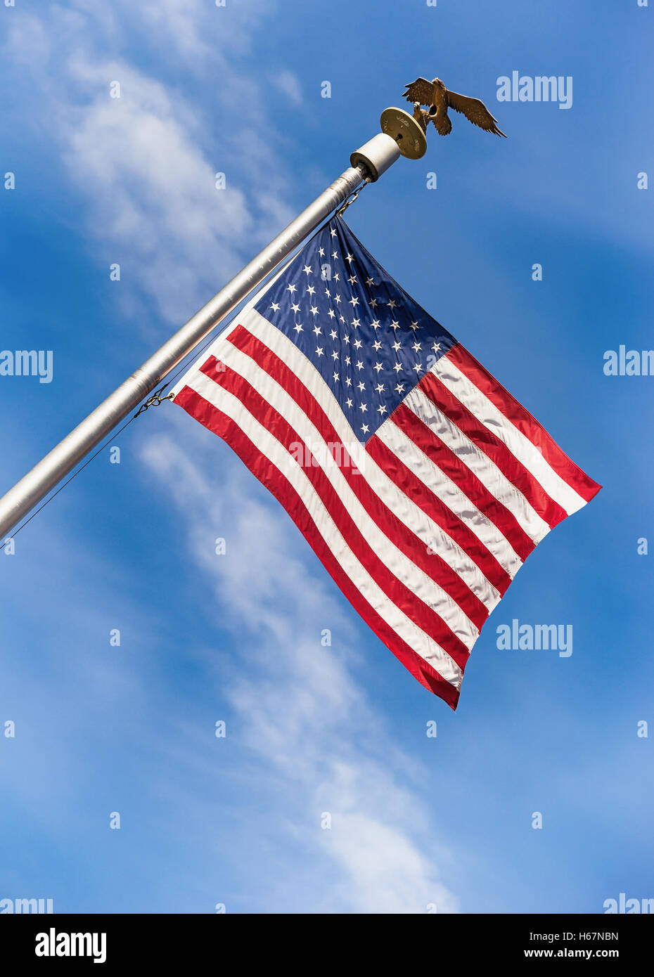 American flag on pole waving in the wind against blue sky background - Stock Image