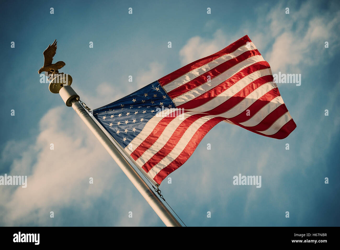 American flag on pole waving in the wind against blue sky and white clouds background - Stock Image