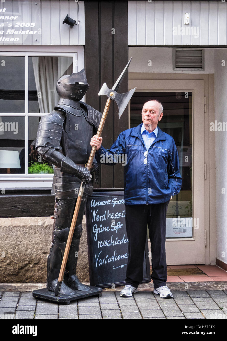 Senior man standing with Suit of armor outside restaurant in Hann. Münden, Lower Saxony, Germany - Stock Image