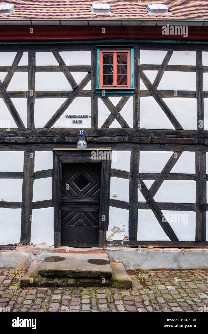 Typical Timber-frame house exterior & door in cobbled street of old town of Michelstadt, Southern Hesse, Germany - Stock Image