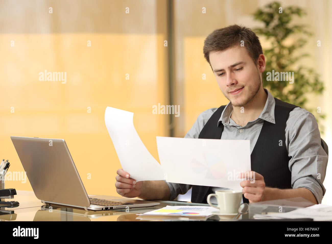 Attentive businessman working comparing paper documents sitting in a desk at office - Stock Image