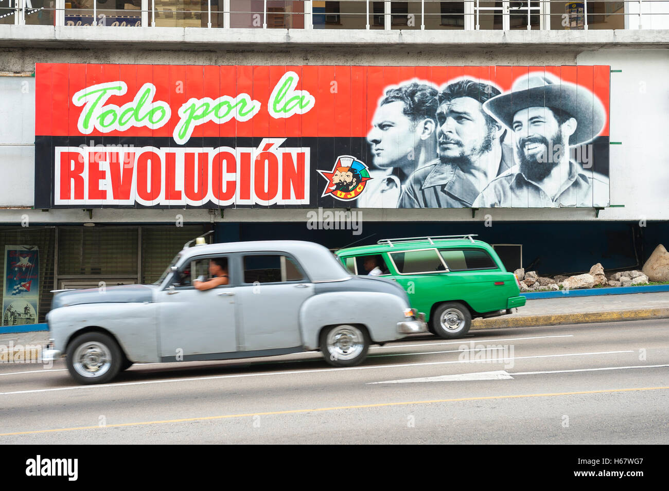 HAVANA - JUNE 13, 2011: Vintage American taxi cars pass below billboard promoting Communist propaganda in La Rampa. - Stock Image