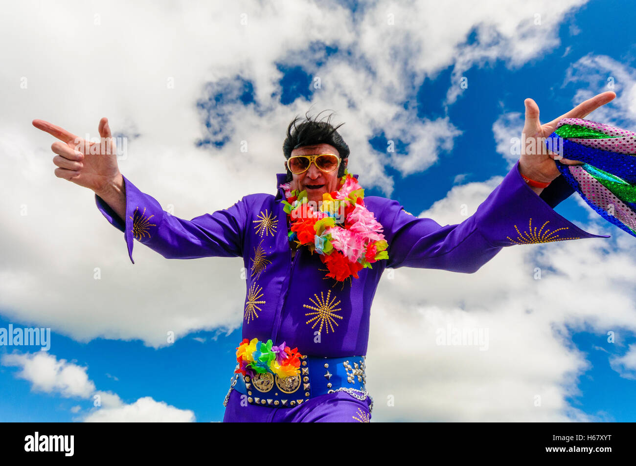 Elvis impersonator wearing a purple jumpsuit, sunglasses and a garland of flowers - Stock Image