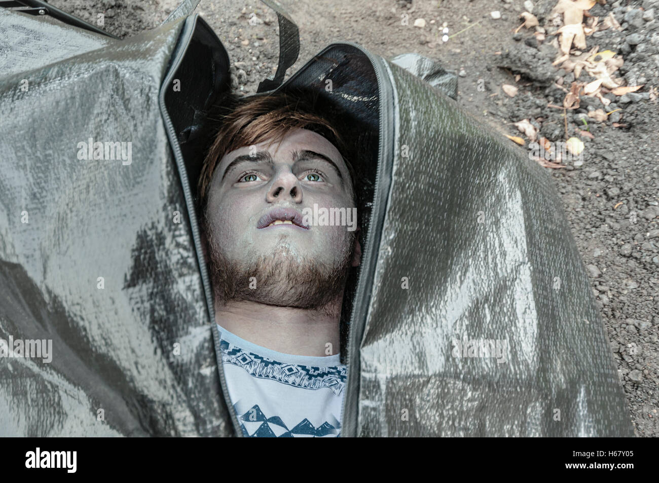 The body of a young man inside a body bag about to be zipped up. - Stock Image