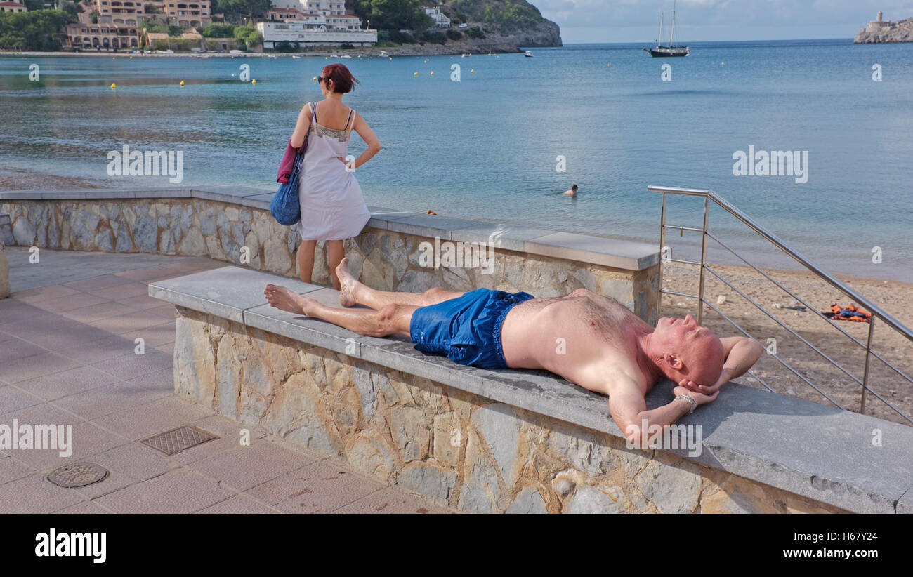 Sunbather and tourist in Soller, Majorca - Stock Image