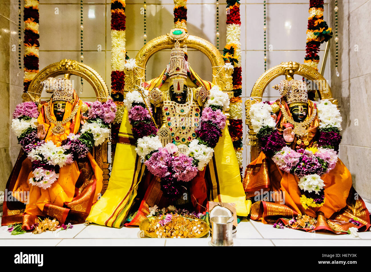Ornate Hindu Deities and gifts at the altar of a Temple. - Stock Image