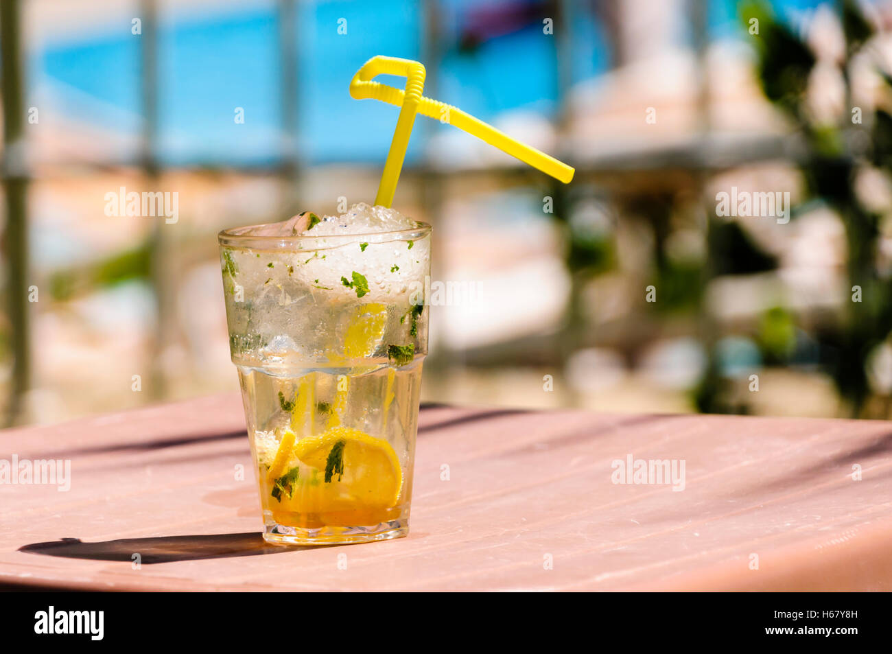 Mojito with yellow straw on the table of a hotel in bright sunlight while on holiday - Stock Image