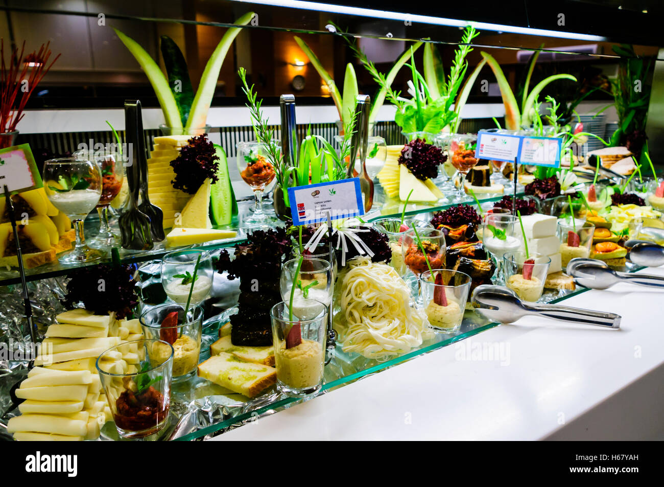 Large selection of cheese with ornate decoration at the buffet of a hotel restaurant - Stock Image