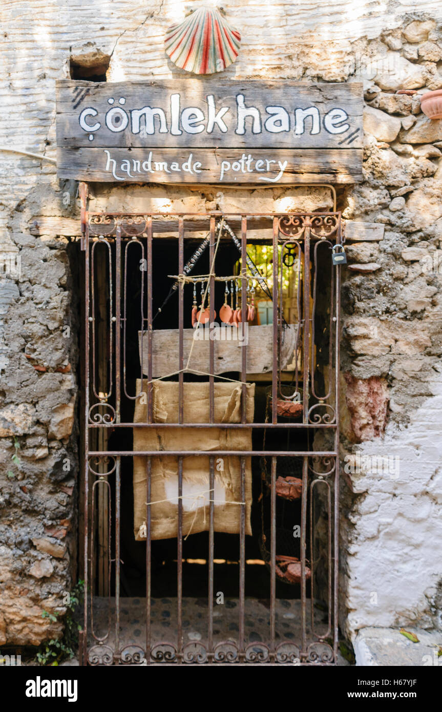 Bars across the entrance of a closed shop selling handmade pottery. - Stock Image