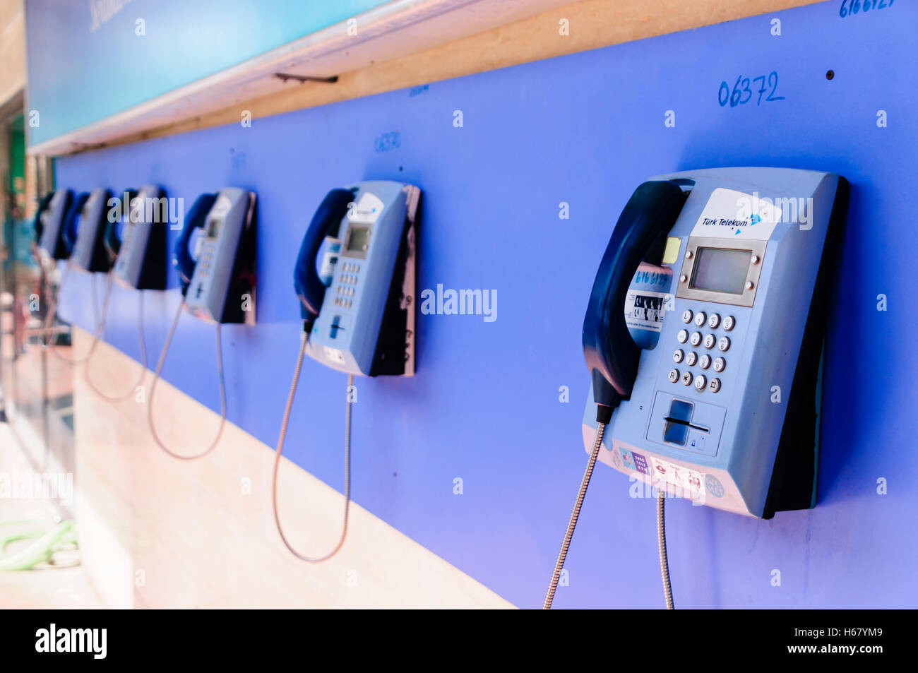 Row of blue Turk Telecom public telephones on a wall - Stock Image