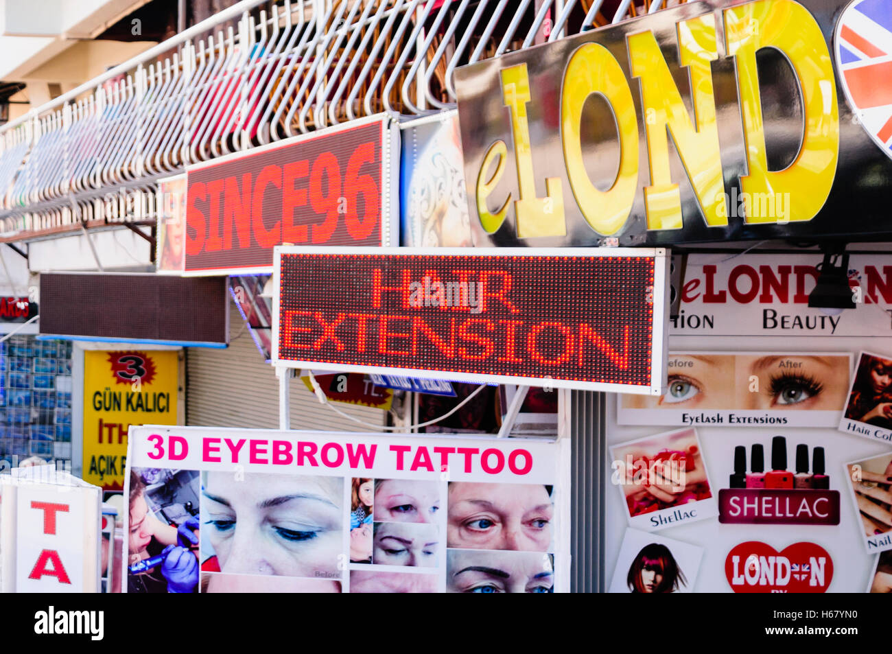 Lots of signs outside a hairdresser advertising Hair Extensions, 3D eyebrow tattoo, nail varnish etc. - Stock Image