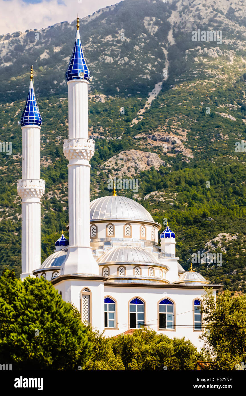 Mosque With Blue Glass Pinnicles On The Miranets At Foot Of A Tall Mountain