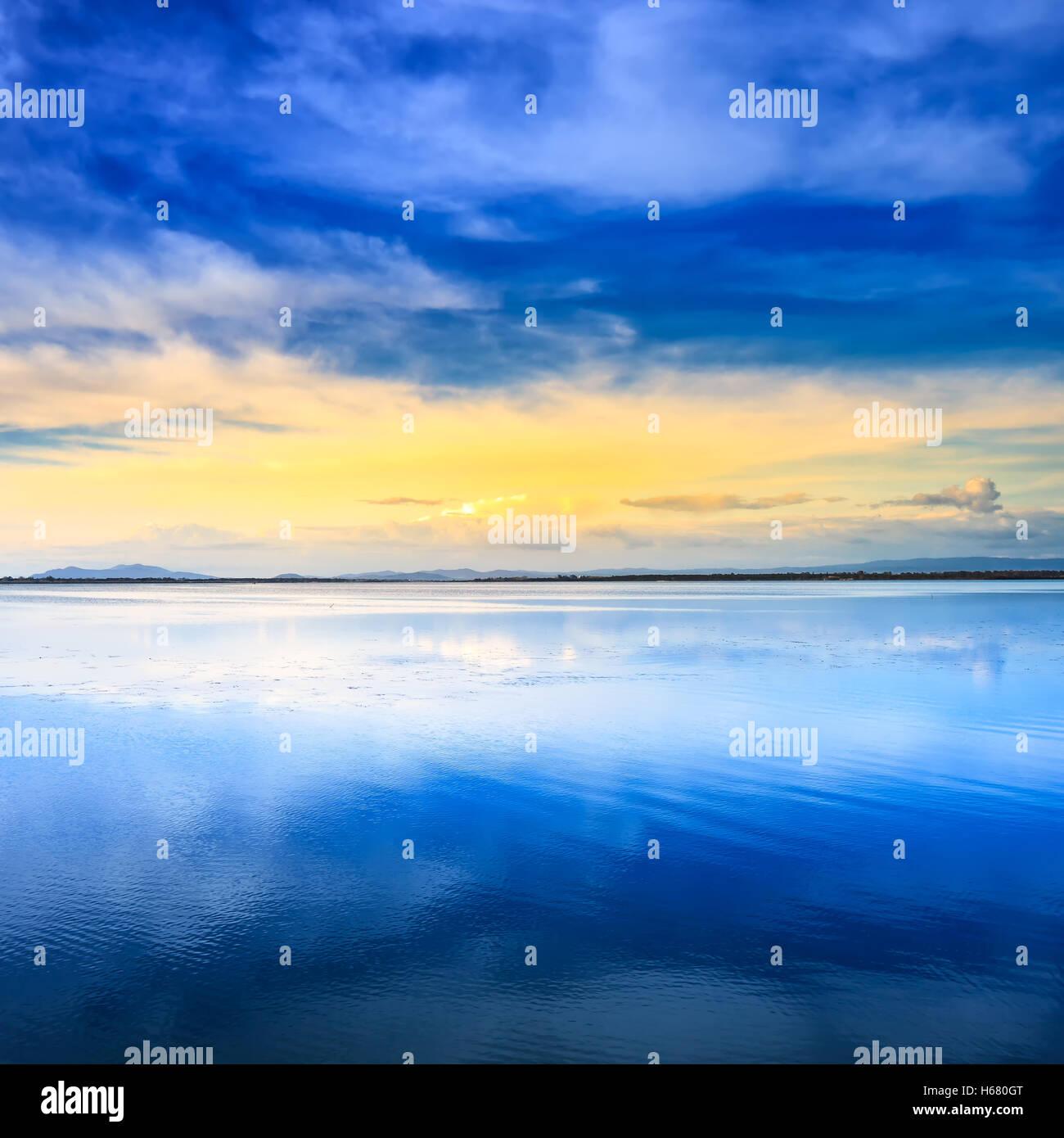 Sunset blue and yellow lagoon landscape. Orbetello lagoon, Monte Argentario, Tuscany, Italy. - Stock Image