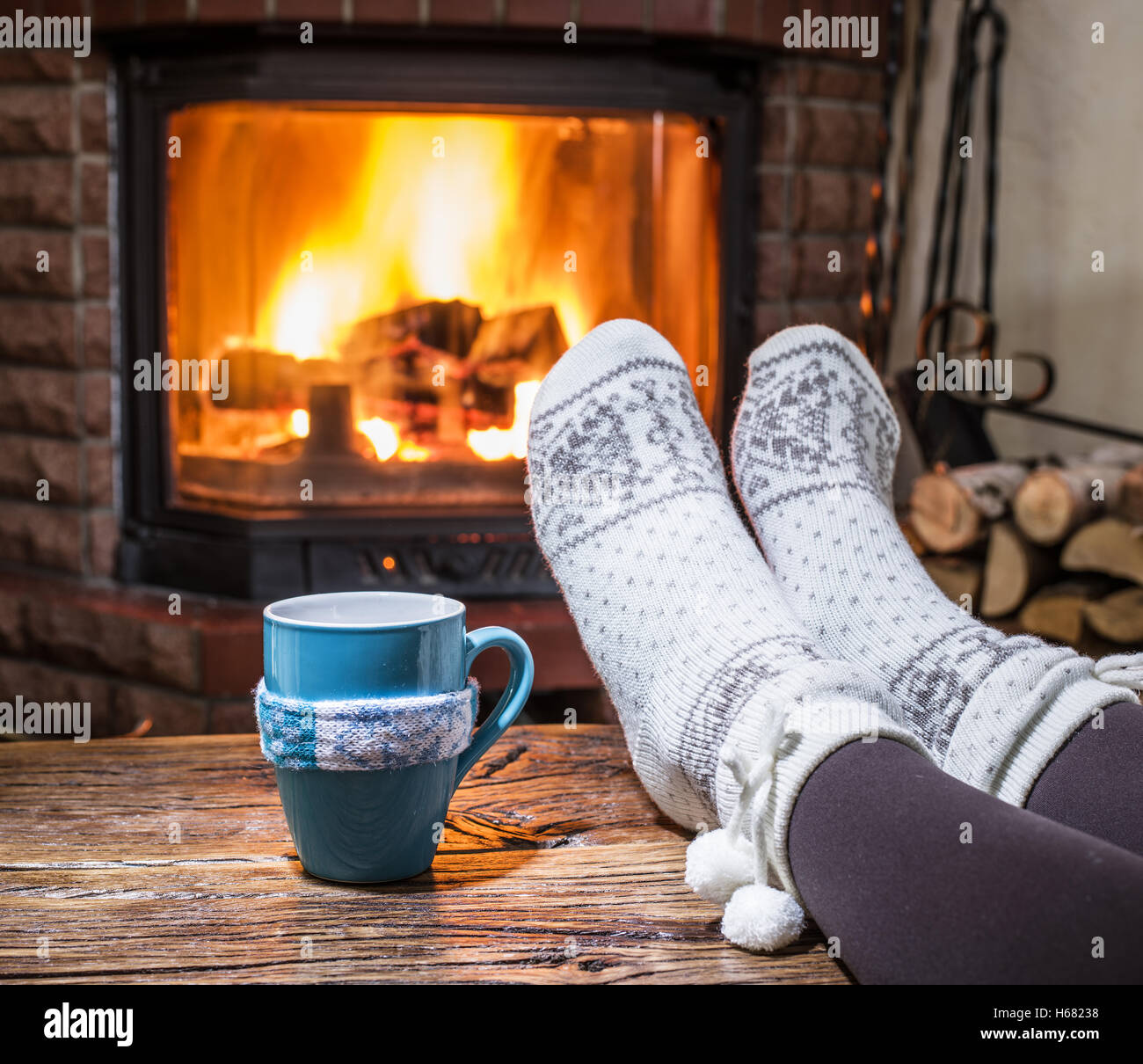 Warming and relaxing near fireplace  Woman feet near the cup