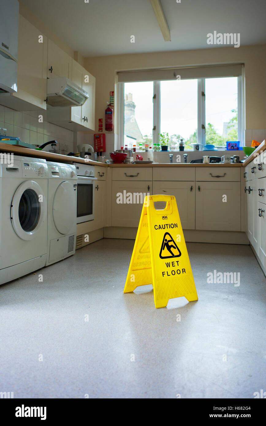 'Caution wet floor' a freestanding yellow Plastic notice board on kitchen floor - Stock Image
