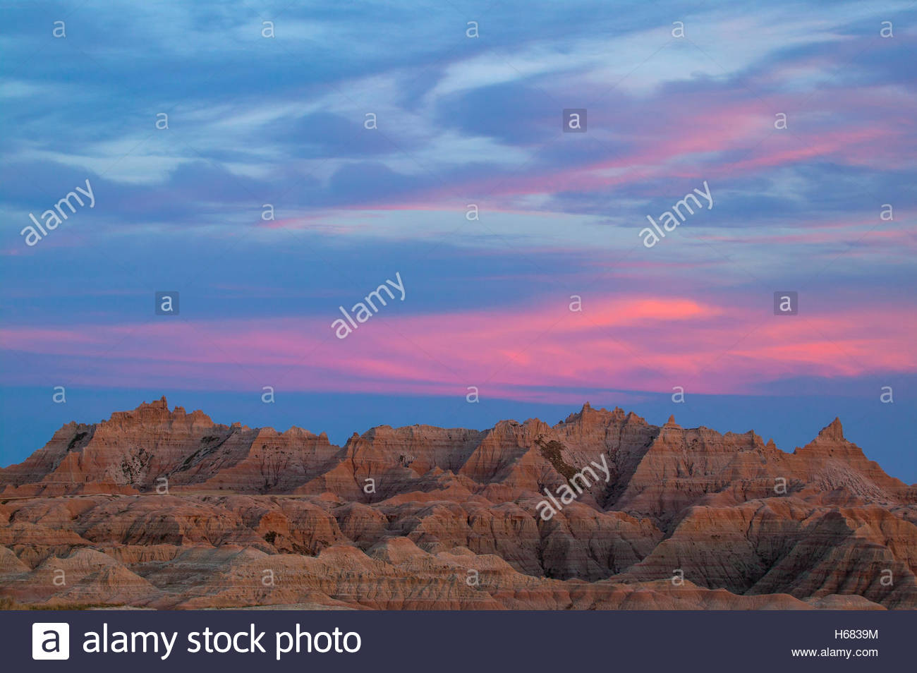 A band of wispy clouds turns pink at dusk over the Badlands in this view over the White River Valley, Badlands National - Stock Image
