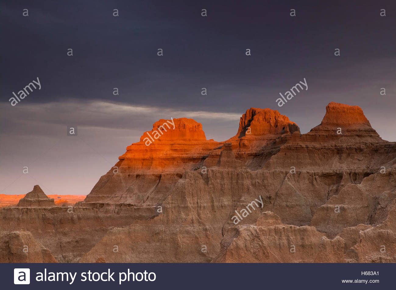 The golden light of sunset shines through a narrow crack in an otherwise dreary fall sky to light up the peaks of - Stock Image