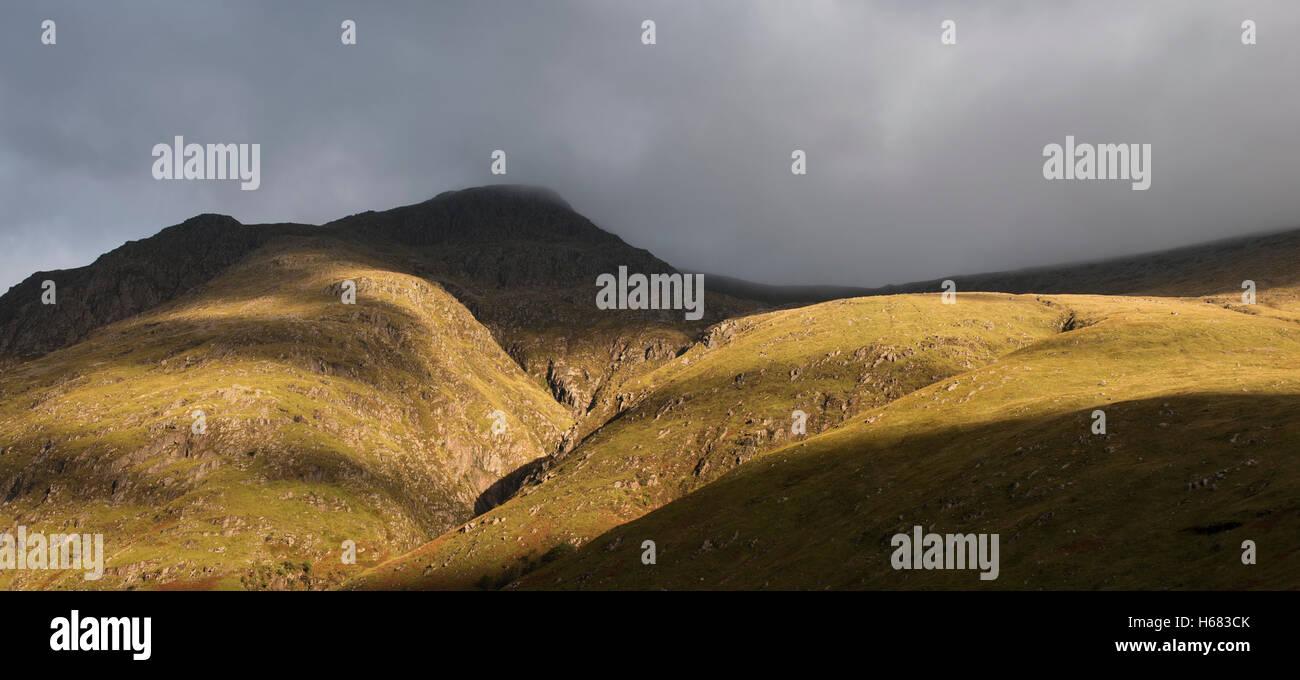 Rain cloud forming thick fog descending from steep mountainside bading in evening light, Glen Coe, Scottish Highlands, - Stock Image