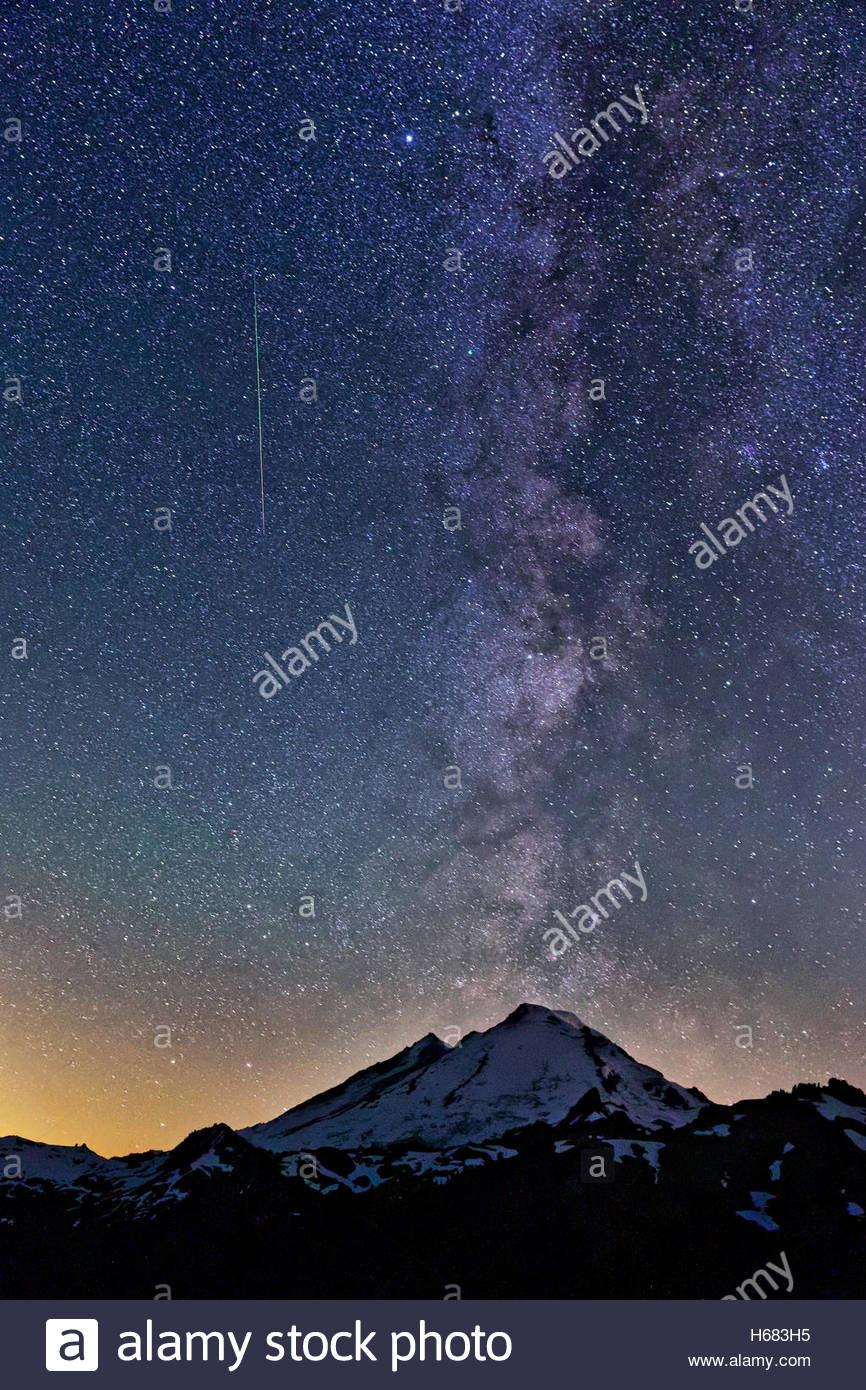 A meteor from the Perseid meteor shower streaks along the Milky Way, which appears to erupt from Mount Baker in - Stock Image