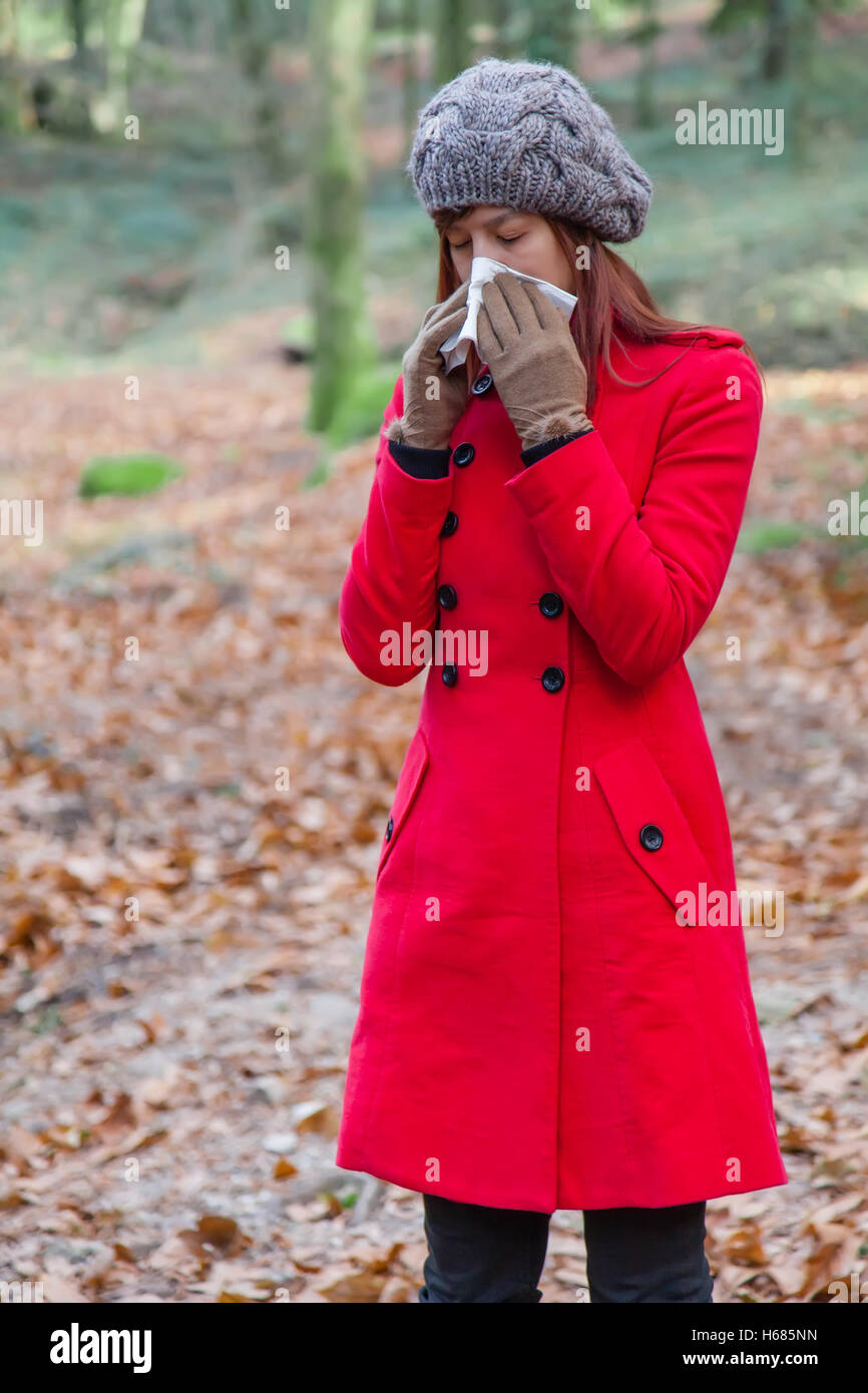 Woman with a cold or flu sneezing to a paper handkerchief on a forest wearing a red overcoat, a beanie and gloves - Stock Image