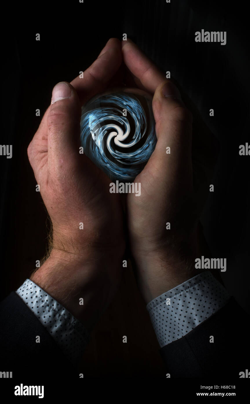 Hands holding magic crystal ball with smoky hypnosis spiral