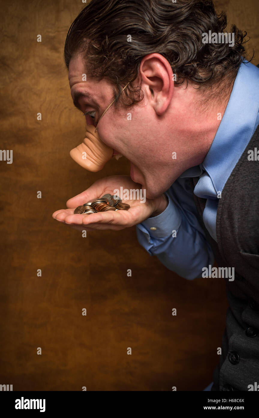 Silly pig man eating lose change for banking greed image - Stock Image