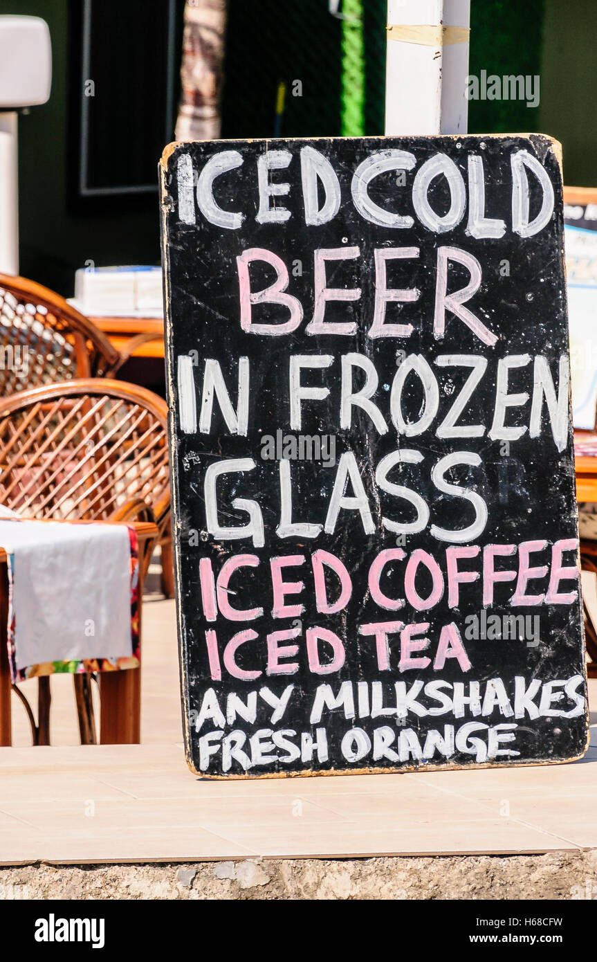 Blackboards outside a bar advertising 'Iced cold beer in frozen glass, Iced coffee, Tea, milk,shakes and fresh - Stock Image