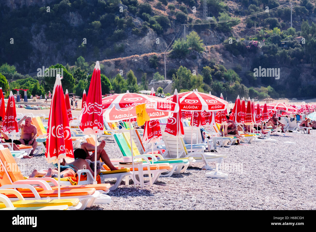 Row of sunloungers and umbrellas on the beach in Oludeniz, Turkey Stock Photo