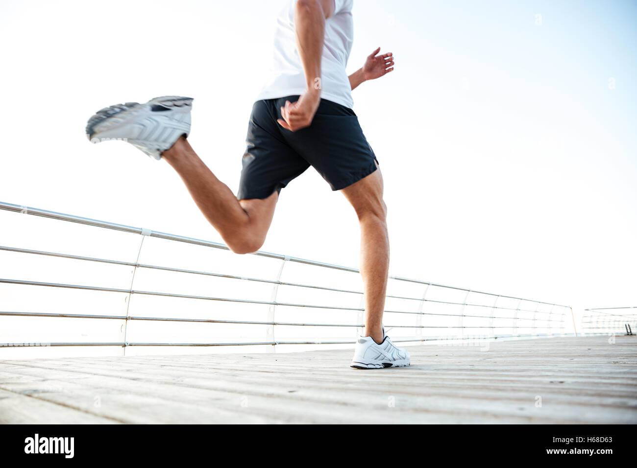 Cropped image of an athlete runner's feet and shoes running along beach pier - Stock Image