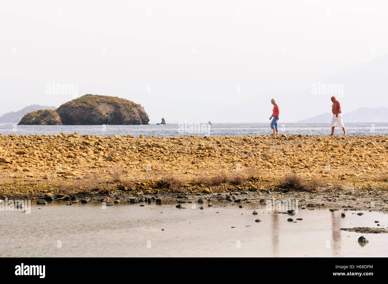 Two people walk along a stony beach on a Turkish island - Stock Image