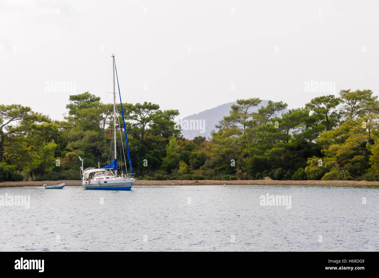 A yacht anchored off the beach of a Turkish tree covered island. - Stock Image