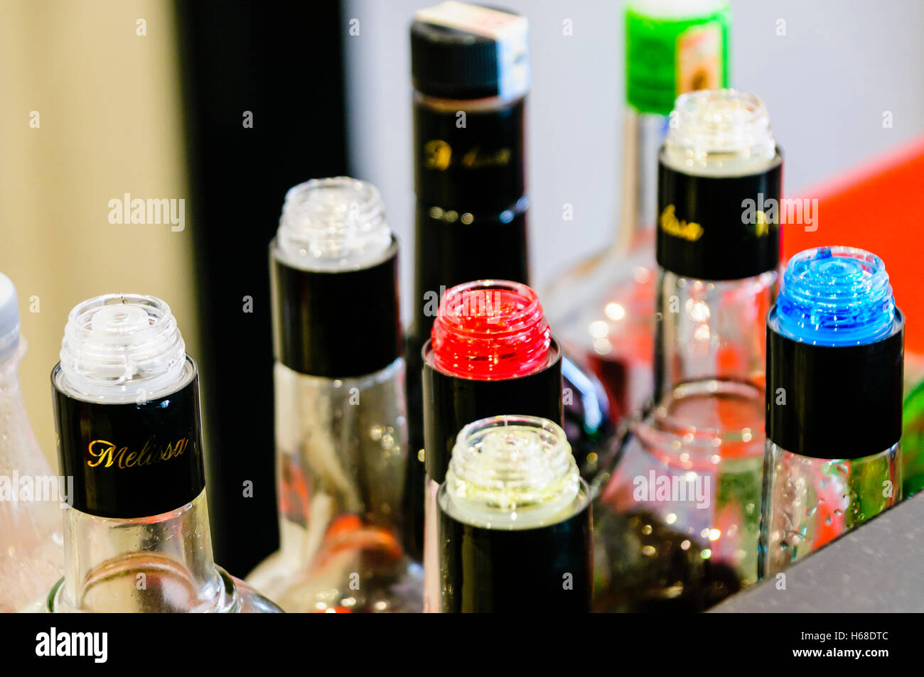 Multicoloured bottles on the counter of a bar with plastic flow restrictors/speed pourers to ensure accurate pouring - Stock Image