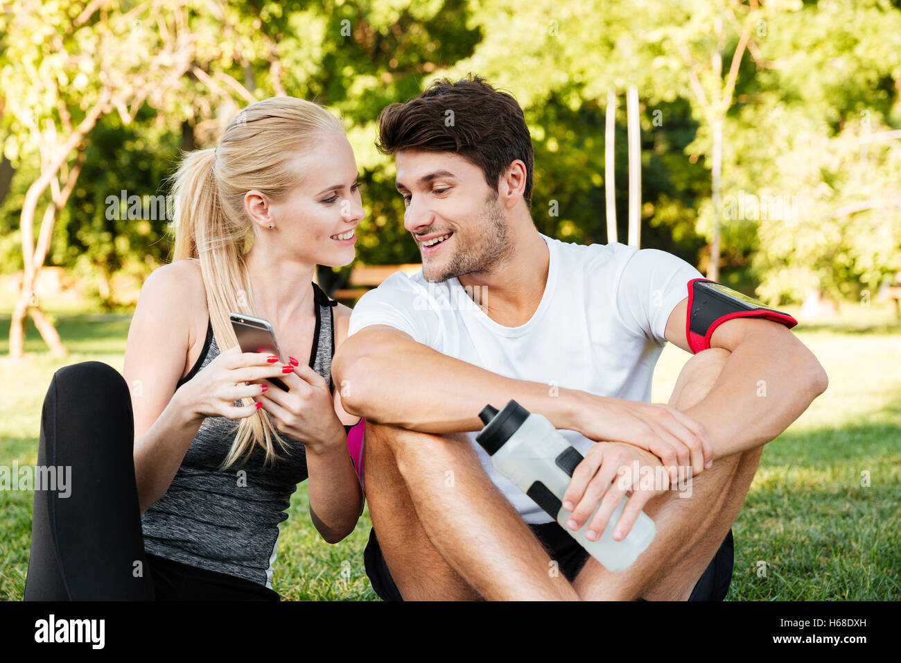Smiling young woman and personal trainer with smartphone resting after jogging outdoors - Stock Image