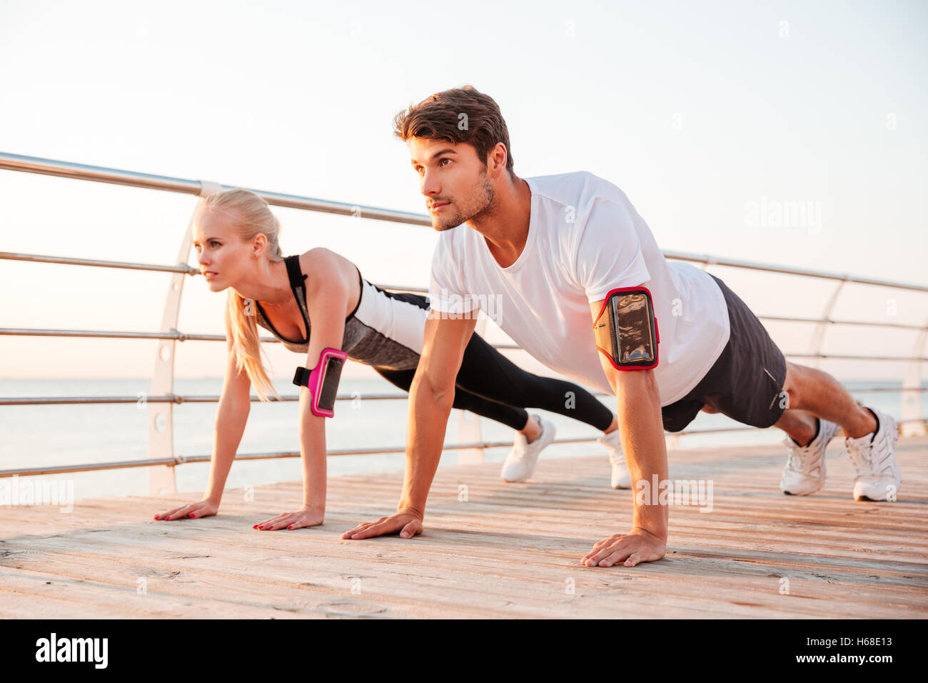 Young sports woman and man doing plank exercise together outdoors at the pier - Stock Image