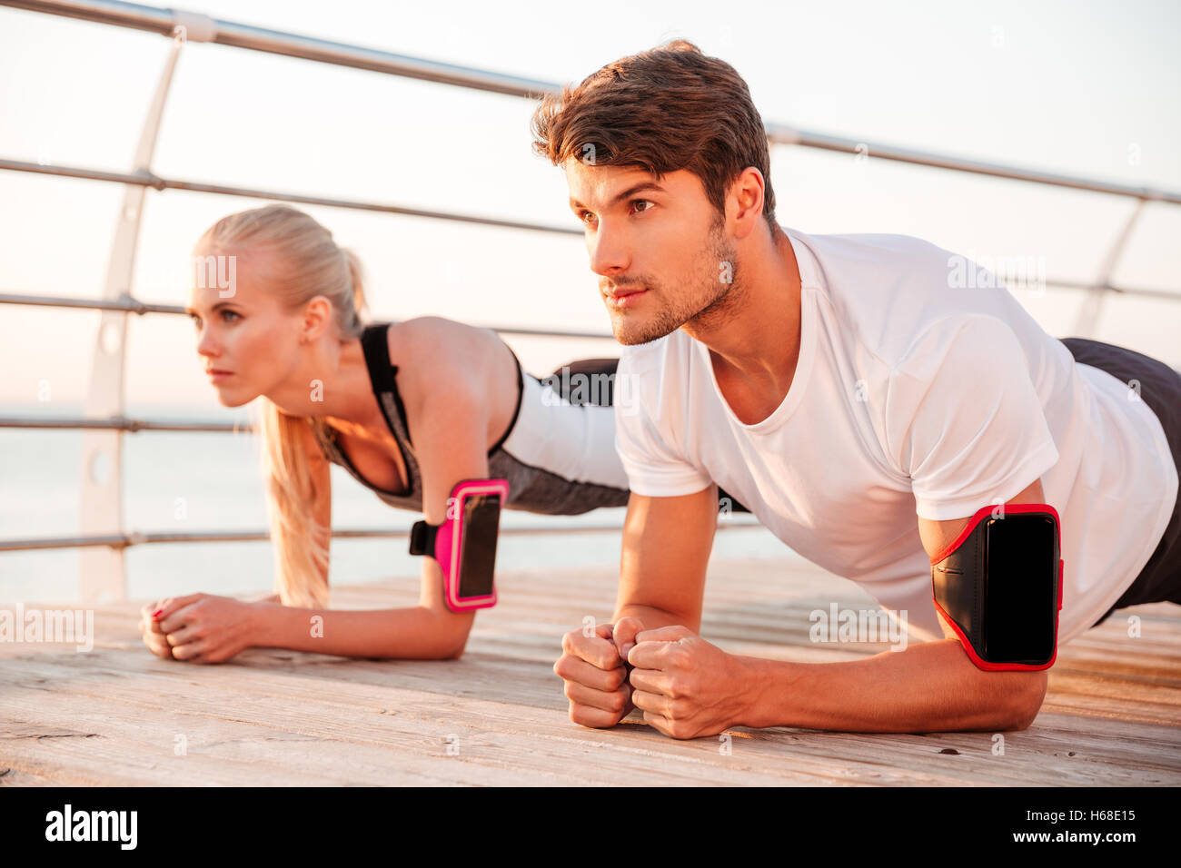 Close up of a young sports woman and man doing plank exercise together outdoors at the pier - Stock Image