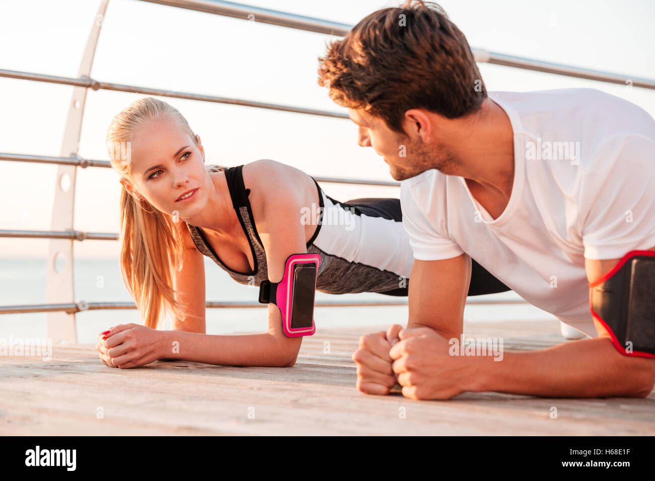 Close up of a young fitness woman and man doing plank exercise together outdoors at the pier - Stock Image