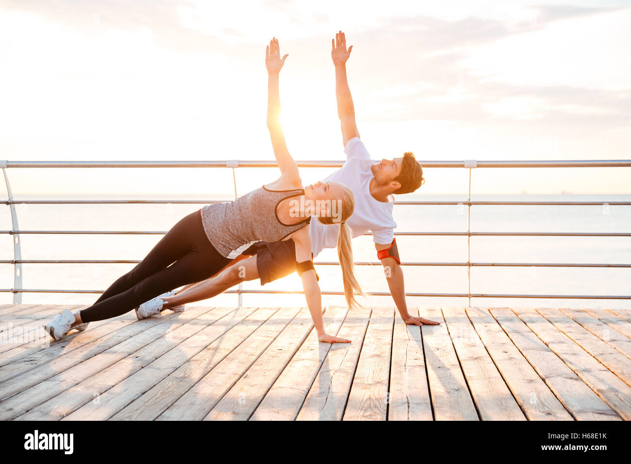 Smiling couple doing yoga exercises outdoors at the beach pier - Stock Image