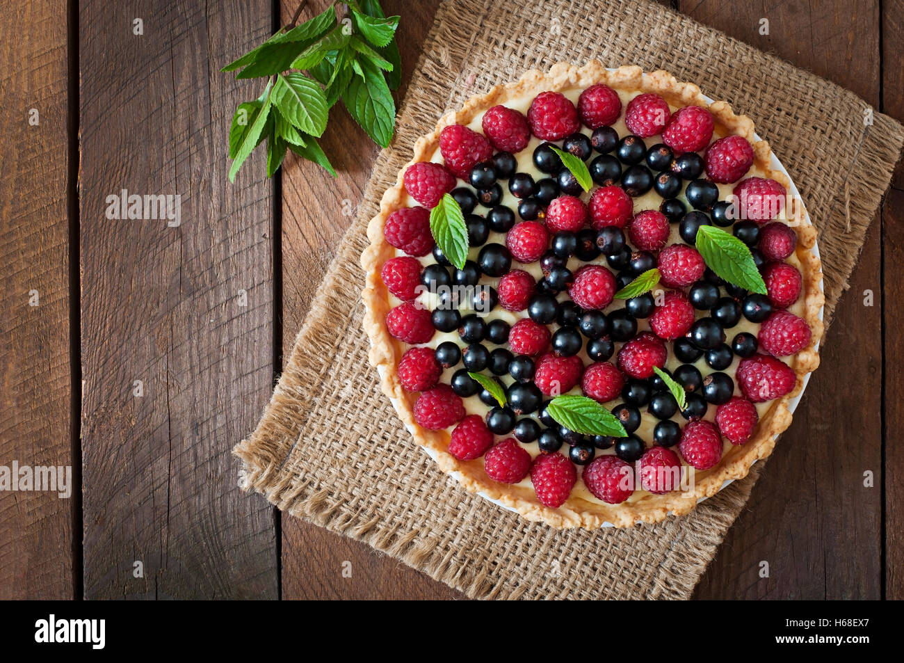 Tart with berries and custard. Top view - Stock Image
