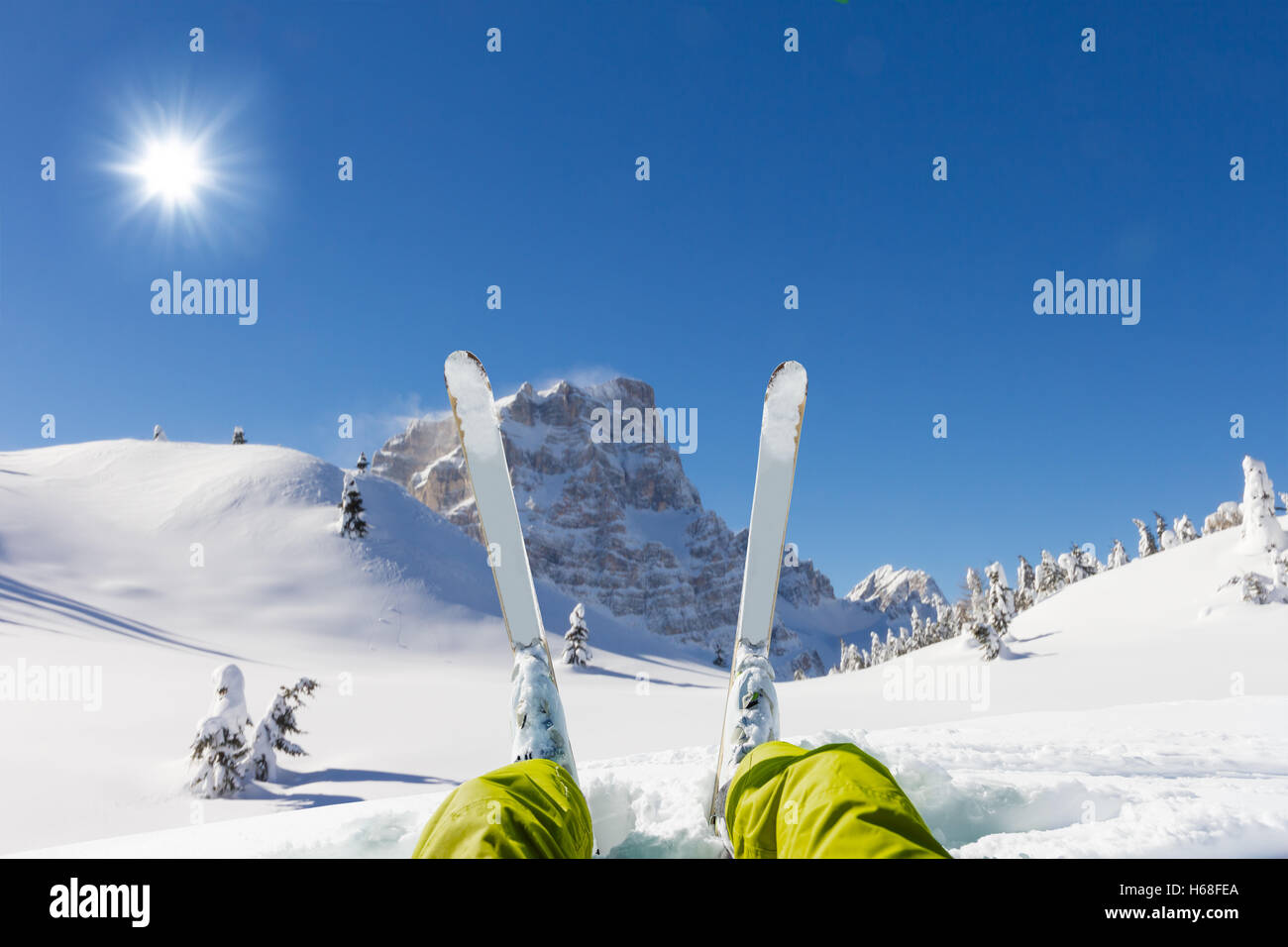 Detail of alpine skier legs, watching the valley panorama. Winter equipment, vacation concept, copyspace for text - Stock Image