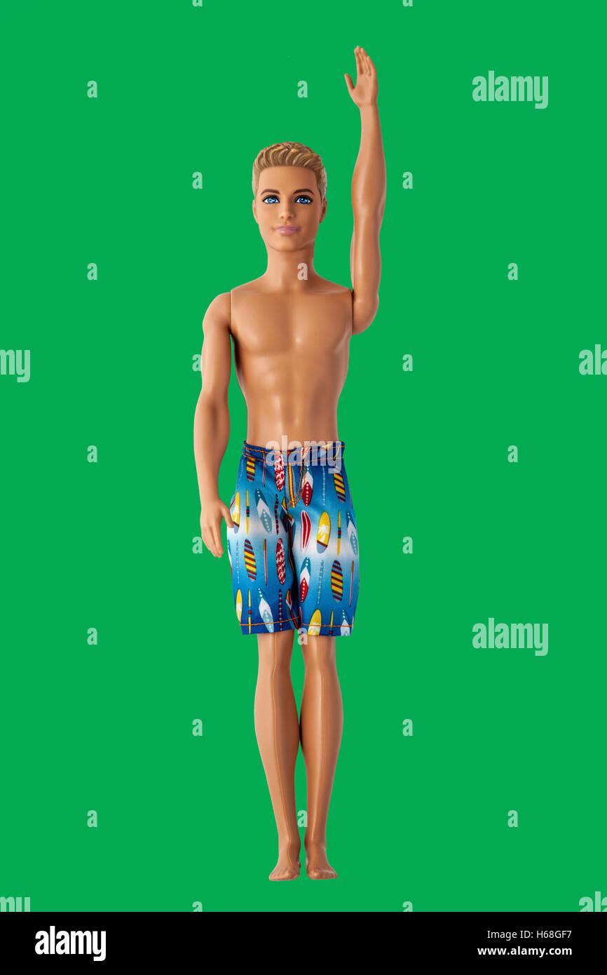 Barbie's boyfriend Ken wearing beach shorts one arm raised. Chromakey green background. - Stock Image